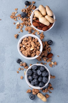 Top view of bowls with breakfast cereal and blueberries