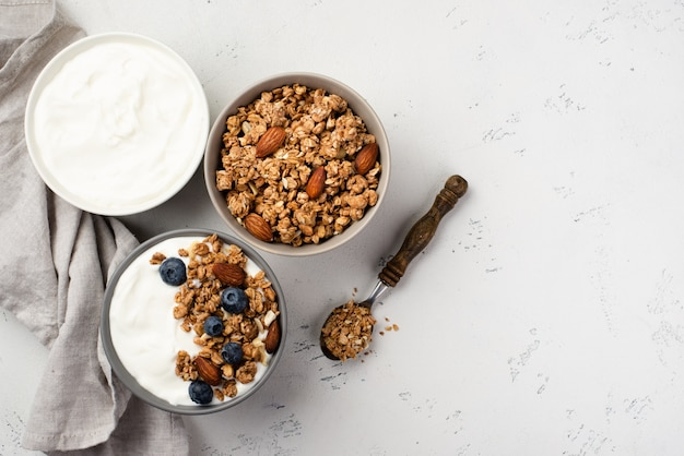 Top view of bowls with breakfast cereal and yogurt