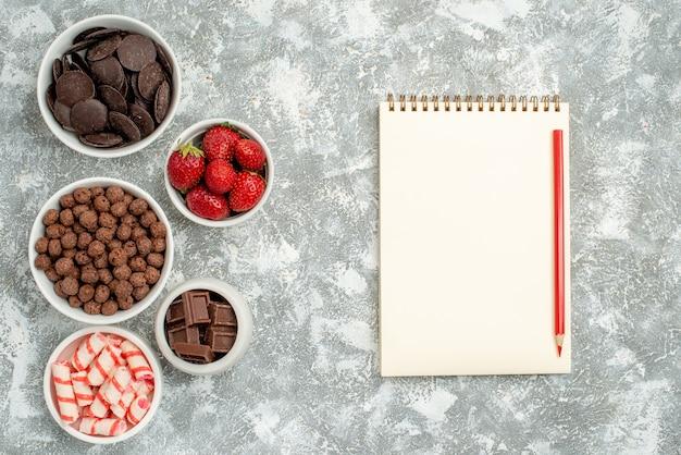 Vista dall'alto ciotole con caramelle fragole cioccolatini cereali e cacao a sinistra e un taccuino con matita rossa a destra del tavolo grigio-bianco