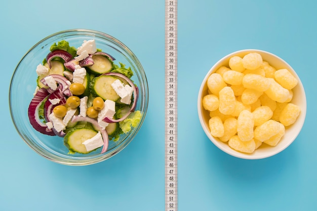 Top view bowls with salad and puffs