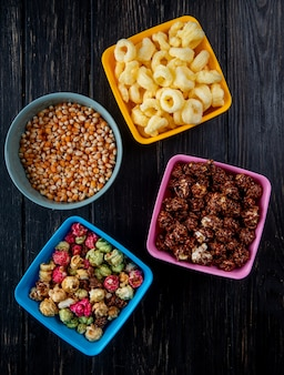 Top view of bowls with skittles and chocolate popcorns corn pop cereals and corn seeds on black surface
