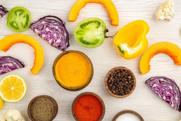 향신료와 상위 뷰 그릇 잘라 노란 피망 콜리 플라워는 붉은 양배추를 잘라 나무 테이블에 녹색 토마토를 잘라