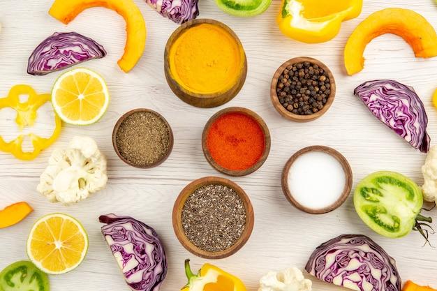 향신료와 상위 뷰 그릇 잘라 노란색 피망 잘라 레몬 콜리 플라워 잘라 붉은 양배추 나무 테이블에 녹색 토마토를 잘라