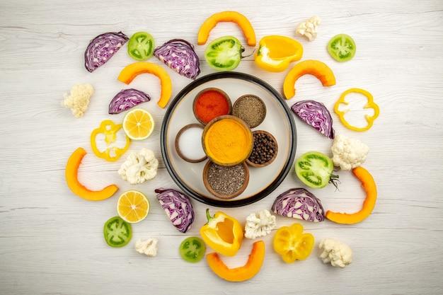 Vista dall'alto ciotole con spezie sul piatto rotondo curcuma sale pepe nero pepe rosso verdure tritate sulla superficie bianca