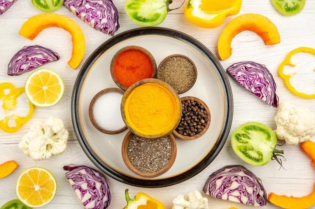 Vista dall'alto ciotole con spezie sulla piastra rotonda curcuma sale pepe nero pepe rosso tagliare le verdure sulla superficie bianca