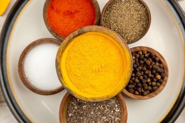 Vista dall'alto ciotole con spezie sul piatto rotondo curcuma sale pepe nero pepe rosso su superficie bianca