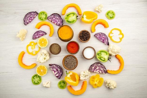 Вид сверху миски со специями куркума черный перец соль красный перец порошок нарезанные овощи на белой поверхности