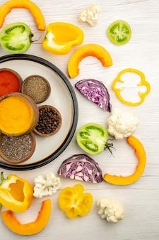Vista dall'alto ciotole con spezie su verdure tritate piatto bianco su superficie bianca