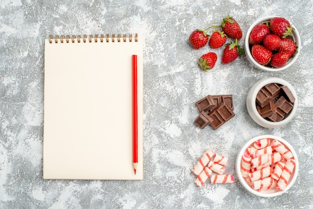 Top view bowls with strawberries chocolates candies and some strawberries chocolates candies at the right side and notebook with red pencilat the left side of the grey-white ground