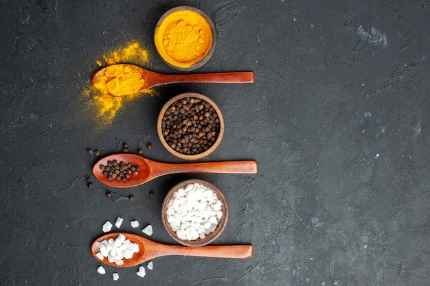 Top view bowls with turmeric black pepper sae salt wooden spoons on black table free space