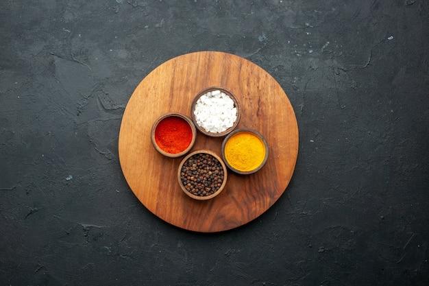 Вид сверху чаши с куркумой, красным перцем, черным перцем, морской солью, круглая доска на темном столе, свободное пространство