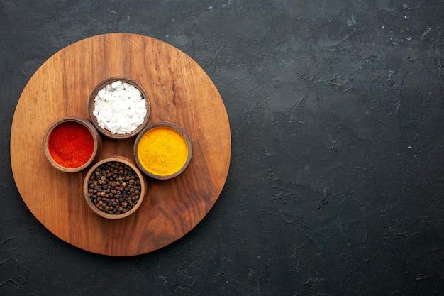 コピースペースのある暗いテーブルにターメリック赤胡椒黒胡椒海塩ラウンドボードとトップビューボウル
