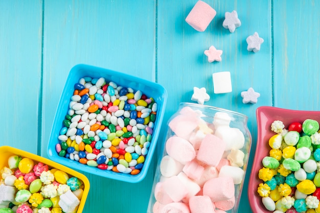 Top view of bowls with various colorful candies and marshmallow scattered from a glass jar on blue background