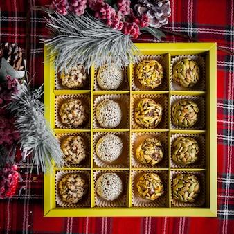 Вид сверху коробка сладкого запеченная с рябиной и еловыми листьями в таблице