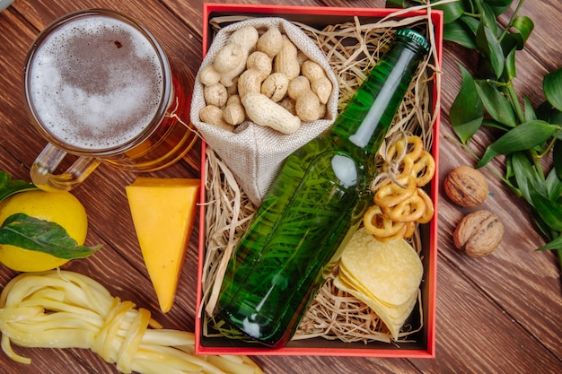 Top view of a box with a bottle of beer peanuts potato chips mini pretzels and straw on rustic with a mug of beer  cheese and lemon