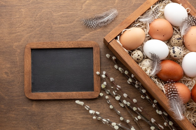Top view of of box with eggs for easter and blackboard