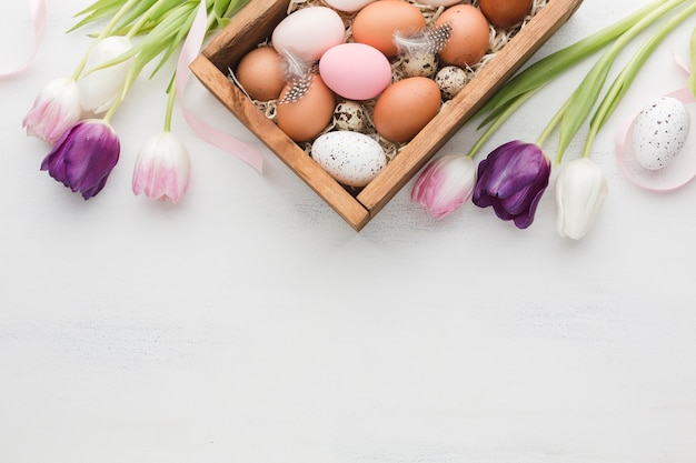 Top view of box with eggs for easter and colorful tulips