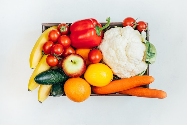 Top view of a box with vegetables and fruits on a white surface