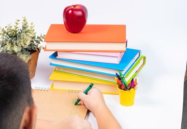 Вид сверху мальчик, рисование на пустой альбом с стопкой книг / обратно в школу концепции