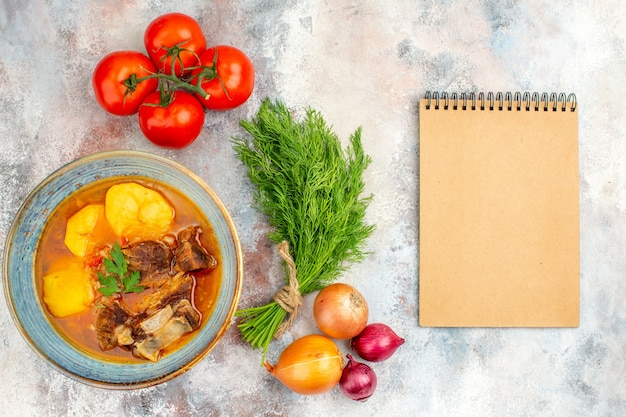 Vista dall'alto zuppa bozbash un mucchio di aneto pomodori cipolle un quaderno su sfondo nudo