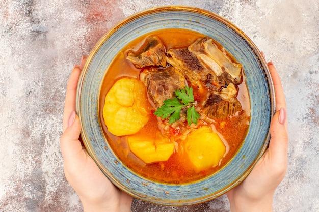 裸の背景に女性の手でボウルにbozbashスープの上面図