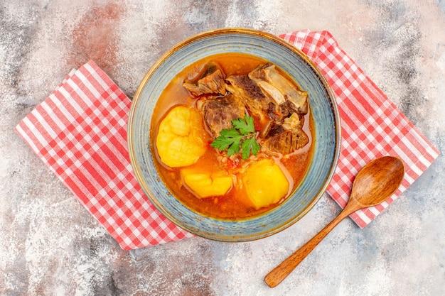 Asciugamano da cucina per zuppa bozbash vista dall'alto un cucchiaio di legno su sfondo nudo
