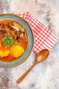 Zuppa di bozbash vista dall'alto un asciugamano da cucina con cucchiaio di legno su sfondo nudo