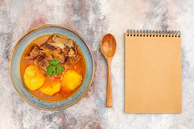Vista dall'alto zuppa di bozbash un cucchiaio di legno un quaderno su sfondo nudo