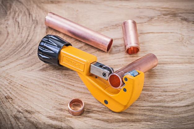 Top view of brass water pipe cutter on wooden board plumbing concept