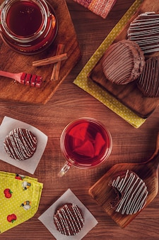 Top view of brazilian honey cookie chocolate covered on the wooden table with a translucent mug of tea, honey bee and cinnamon - pã£o de mel