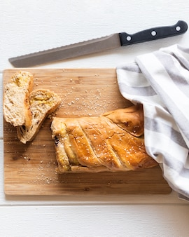 Top view of bread and knife on plain background