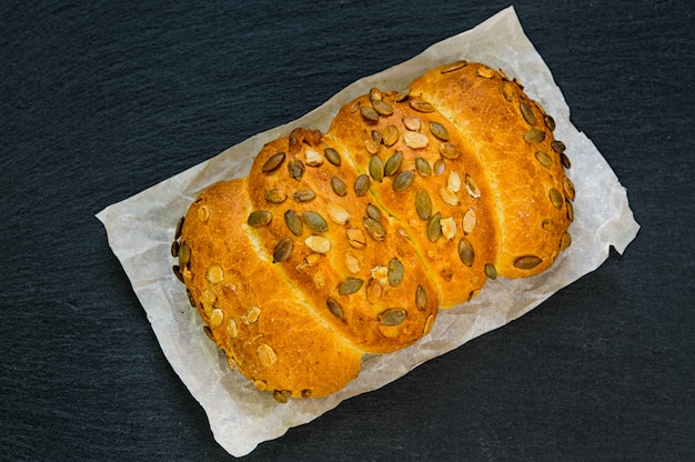 Top view of bread loaf with pumpkin seeds on black slate stone board