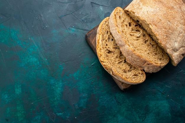 濃紺の机の上で焼いてスライスしたおいしいパンの上面図。
