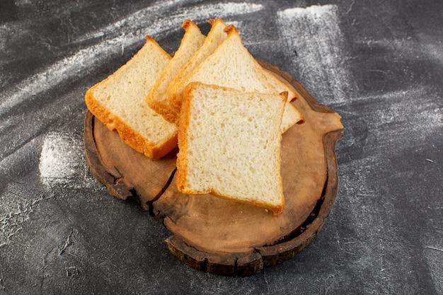 トップビューパンは茶色の木製の机と灰色の背景の生地のパンのパンに白パンをloafs