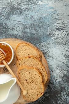 明るい表面の朝食用食品の甘い蜂蜜とトップビューのパン