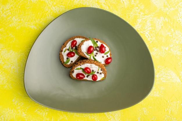 Vista dall'alto di pagnotte di pane con panna acida all'interno del piatto verde sulla superficie gialla