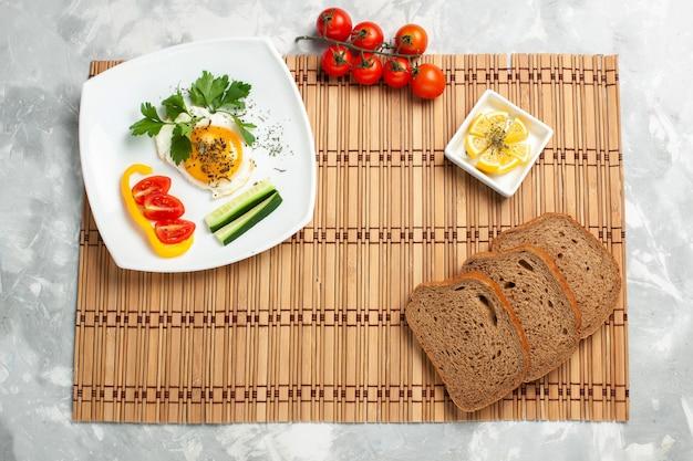 Pagnotte di pane vista dall'alto con verdure e verdure sulla scrivania bianco chiaro