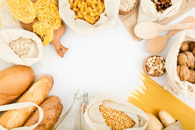 Top view of bread in reusable bag with bulk pasta and assortment of nuts