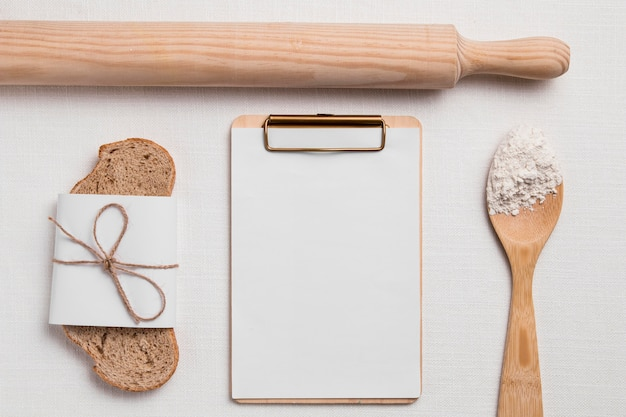 Top view bread slice with blank clipboard and rolling pin