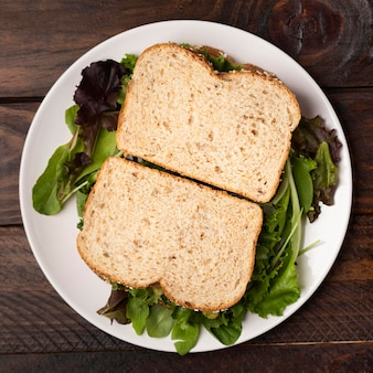 Вид сверху ломтики хлеба на листьях салата