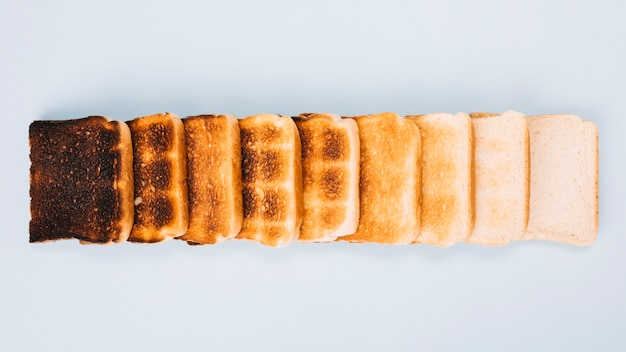 Top view of bread slices at varying stages of toasting arranged in row on white background