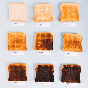 Top view of bread slices at varying stages of toasting on white background