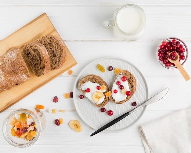 Вид сверху ломтики хлеба с йогуртом и фруктами