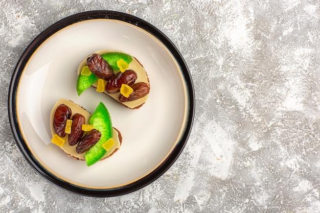 흰색 책상 빵 토스트 샌드위치 음식 아침 식사에 접시 안에 오이와 말린 자두와 상위 뷰 빵 토스트