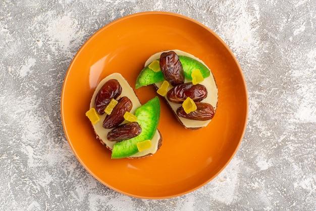 Vista dall'alto toast di pane con cetriolo e prugne secche all'interno della piastra arancione sulla parete bianca pane tostato sandwich cibo colazione