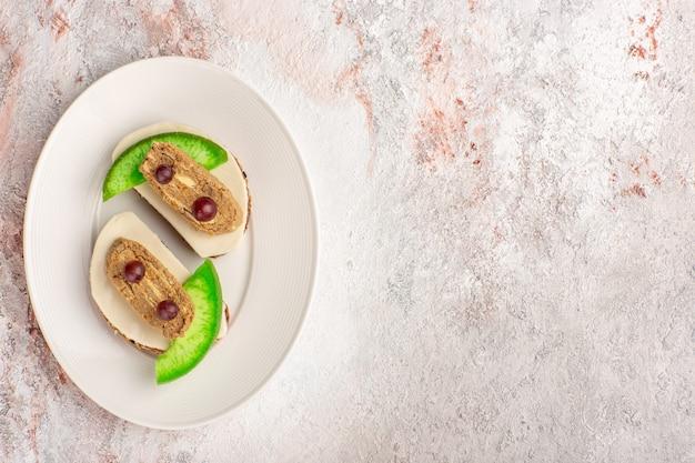 白い机の上のプレートの内側にパテとキュウリのスライスが付いた上面図のパントースト肉野菜料理食事トーストサンドイッチ