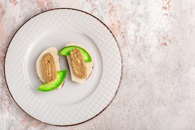 白い壁の肉野菜料理ミールトーストサンドイッチのプレートの内側にパテとキュウリのスライスが付いた上面図のパントースト