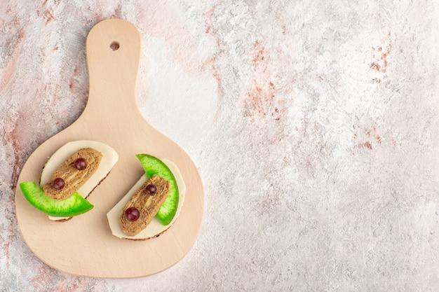 白い壁の肉野菜食品トーストサンドイッチのプレートの内側にパテとキュウリのスライスが付いた上面図のパントースト