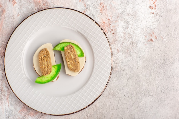 Top view bread toasts with pate and cucumber slices inside plate on the white wall meat vegetable food meal toast sandwich