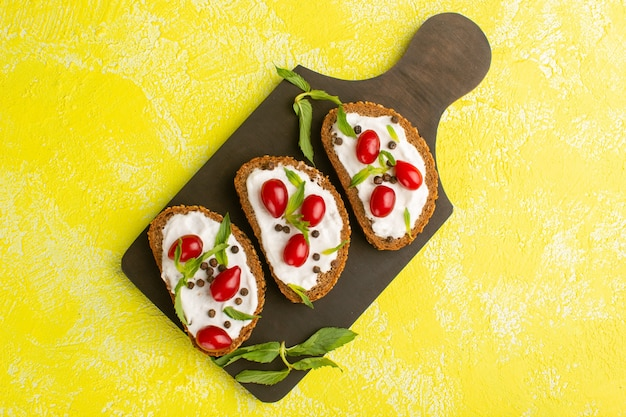 Top view of bread toasts with sour cream and dogwoods on the yellow desk